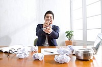 Businessman with crumpled paper at desk