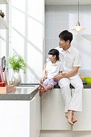Father and daughter sitting on kitchen counter