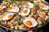 Fried eggs with potatoes. April fair. Barcelona. Catalonia. Spain.