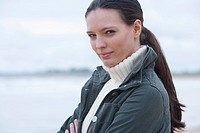 Portrait of confident young woman with arms crossed on beach