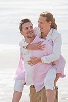 Smiling couple piggybacking on sunny beach