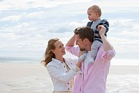 Smiling young couple holding baby son on sunny beach