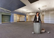 Mixed race businesswoman standing with garbage cans in empty office