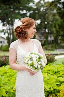 Smiling Caucasian bride holding wedding bouquet