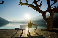 Man sitting on a bench and watching a sunset on alpine lake Maggiore with mountain in Ascona, Switzerland.