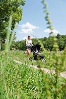 Germany, Munich, Mother jogging with baby boy in pram