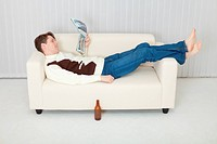 Person comfortably lie on sofa with beer and journal