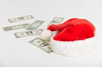 Christmas cap and dollars on white background