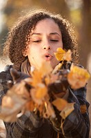 Caucasian woman blowing autumn leaves