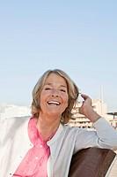 Spain, Mallorca, Senior woman sitting on bench at sea shore, smiling, portrait