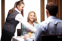 Waitress serving business people in cafe