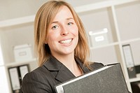 Young woman with folder in office, smiling, portrait