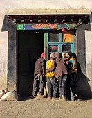 Children cluster round a traditional house window and door to glimpse a video film Sakya Tibet