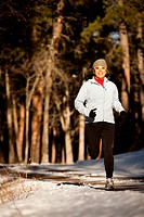 a Japanese_American woman runs through a glade of trees along a dirt road in evening light in Custer State, South Dakota.