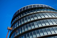 England, London, Southwark. A workman performing maintenance from a cherry picker on a window of City Hall, home of the Greater London Authority GLA c...