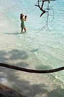 Asian tourist barefoot in the sea using a video camera, Similan Islands, Andaman Sea, Thailand