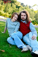 Young couple sitting on the grass in a park