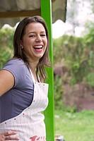 Laughing Hispanic woman wearing apron