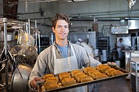 Caucasian baker carrying tray of croissants in bakery