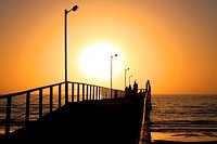 Orange Sunset behind People Walking along Larg´s Bay Jetty, Adel