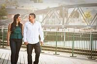 Hispanic couple walking on urban bridge