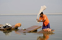 A Dhobi wala, a man of the laundry cast, doing laundry at the ghats along the holy river Ganges, Varanasi, Uttar Pradesh, India, Asia