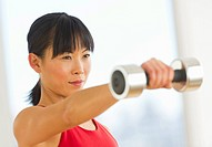 Mid adult woman exercising with dumbbells