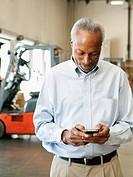 Businessman using phone in warehouse