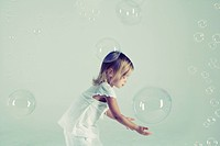 Studio shot of girl playing with bubbles