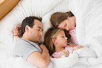 Parents with daughter 12_13 sleeping in bed