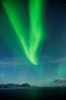 Northern Lights fill sky over sea and mountains, Stamsund, Vestvagoy, Lofoten islands, Norway
