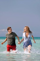 Couple walking in water, holding hands
