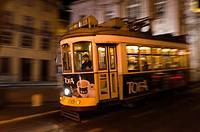 Tram in the night cross Alfama district in Lisbon, Portugal