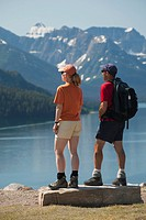 male and female hikers standing on a rock looking out onto a lake with mountains and blue sky, waterton alberta canada