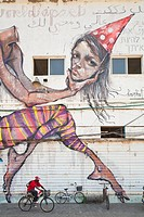 Israel, Tel Aviv, Jaffa, cycliste along an old warehouse covered with mural in one of the oldest ports in the world