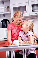 Two girls, sisters having breakfast in the kitchen
