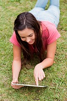 Young smiling woman lying down in a park while using her tablet pc