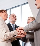 Successful business team putting their hands on top of one another