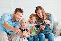 A family playing a games console together as they sit on the couch