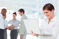 Smiling saleswoman on her laptop with colleagues behind her