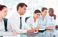 Businesspeople taking notes during a meeting