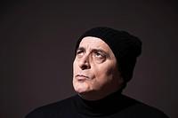 Elderly man wearing a black woollen hat, with an incredulous glance
