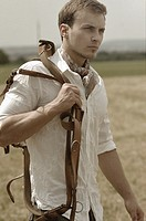 Man wearing riding clothes walking in a field in summer holding a leather strap
