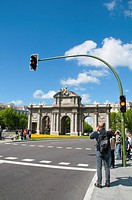 Tourist taking photos at Alcala Gate. Madrid, Spain.