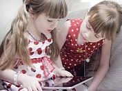 Girls using tablet computer on sofa