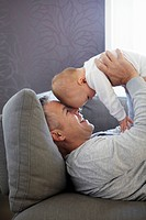 Father and baby relaxing on sofa