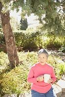 Senior Asian woman sitting in the sunlight drinking tea