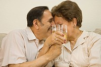 Senior Hispanic couple hugging and toasting with champagne