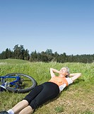 Woman laying in grass next to bicycle