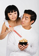 Asian woman taking fortune cookie from boyfriend